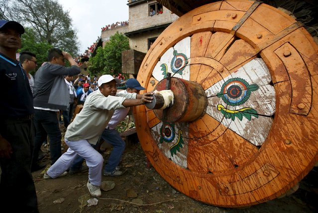 Devotees push the chariot of Rato Machhindranath during the chariot festival at Bungamati in Lalitpur April 22, 2015. Rato Machhindranath is known as the god of rain and both Hindus and Buddhists worship Machhindranath for good rain to prevent drought during the rice harvest season. (Photo by Navesh Chitrakar/Reuters)