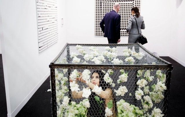 """Artist Romina de Novellis, of Italy, is sits in a screen cage as part of her performance piece """"The Cage"""", in which she is locked in the cage and fills the walls with flowers, during the preview day of the 22nd annual Armory Show art fair at piers 92 and 94 in New York, New York, USA, 02 March 2016. The annual event brings together international galleries and artist to New York each year and runs from 03 March to 06 March. (Photo by Justin Lane/EPA)"""