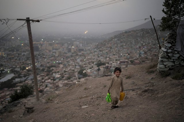 A boy carries water to his home atop a hill in Kabul, Afghanistan, Saturday, September 11, 2021. (Photo by Felipe Dana/AP Photo)