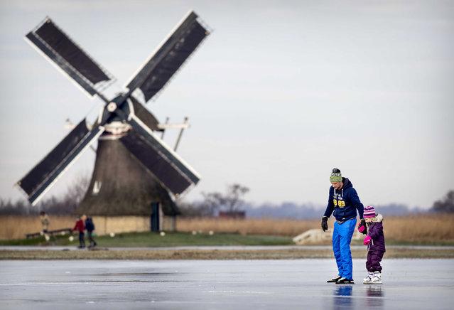 Skating enthusiasts skate on natural ice in the Frisian Ryptsjerkerpolder pond in Ryptsjerk, the Netherlands, 20 January 2019. People enjoy skating on natural ice in Netherlands after sub zero temperatures were noted during nights in the last days. (Photo by Koen van Weel/EPA/EFE)