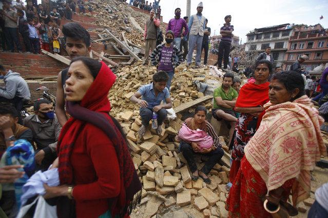 People rest on debris at Durbar Square after an earthquake in Kathmandu, Nepal, Saturday, April 25, 2015. (Photo by Niranjan Shrestha/AP Photo)