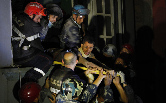 Survivor Rishi Khanal, 27, is freed by French rescuers from the ruins of a three-story hotel in the Gangabu area of Kathmandu, Nepal, Tuesday, April 28, 2015. (Photo by Niranjan Shrestha/AP Photo)