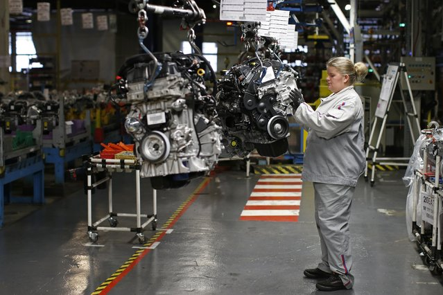 An employee works on an engine on the assembly line of the Peugeot 208, Citroen C3 and DS 3 cars at the PSA Peugeot Citroen plant in Poissy, near Paris, France, April 29, 2015. (Photo by Benoit Tessier/Reuters)