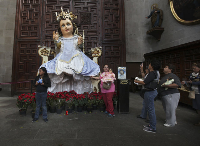 This Thursday, February 2, 2017 photo shows a giant statue depicting baby Jesus, inside the Metropolitan Cathedral in Mexico City. Catholic faithful in Mexico honor the story of the infant Christ being presented before the temple in Jerusalem, 40 days after Christmas, by adorning a figure of baby Jesus in fine clothing and carrying it to Mass to be blessed. (Photo by Marco Ugarte/AP Photo)