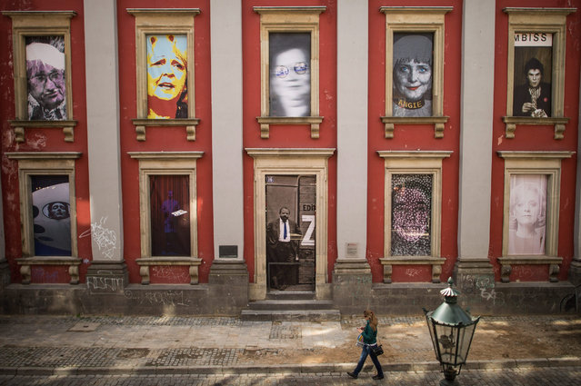 "A pedestrian walks past large-scale painted portrait tableau titled ""Ratinger Freiheit"" (lit. Rating Liberty) in the old town of Duesseldorf, Germany, 29 April 2015. Temporary installed works of art were placed in window frames on the exterior facade of buildings showcasing the portraits of known personalities, amongst others Napoleon Bonaparte, Angela Merkel, Hannelore Kraft, Campino and Claudia Schiffer. (Photo by Maja Hitji/EPA)"