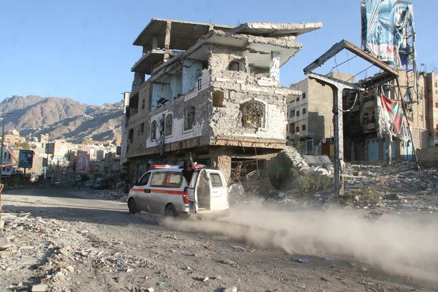An ambulance drives past a building destroyed during recent fighting in Yemen's southwestern city of Taiz March 14, 2016. (Photo by Anees Mahyoub/Reuters)