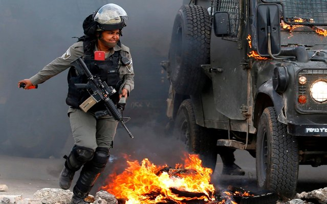 A member of the Israeli security forces runs next to a military jeep set on fire by Molotov cocktails launched by Palestinian protesters during a demonstration on the outskirts of Ramallah in the occupied West Bank on March 27, 2019, in support of Palestinian prisoners held in Israeli jails. (Photo by Abbas Momani/AFP Photo)