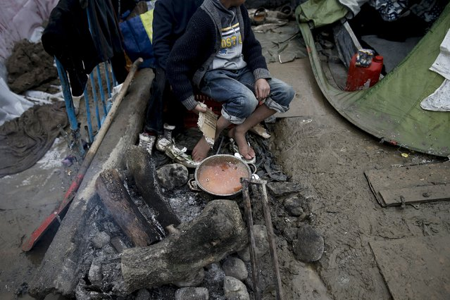 Children sit next to a cooking pot on a bonfire at a makeshift camp for refugees and migrants at the Greek-Macedonian border, near the village of Idomeni, Greece March 15, 2016. (Photo by Alkis Konstantinidis/Reuters)