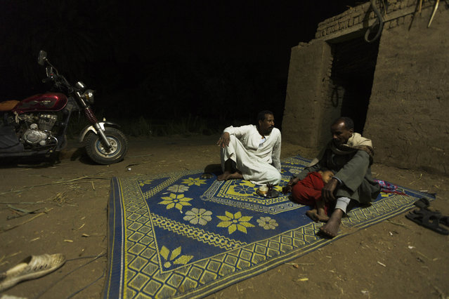 In this Friday, April 17, 2015 photo, Salama Osman, left, chats with his fisherman friend, Sayed Ahmed Abdoh, outside his home in Abu al-Nasr, about 770 kilometers (480 miles) south of Cairo. (Photo by Hiro Komae/AP Photo)