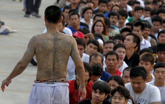 A devotee in a state of trance mimics creatures tattooed on his body during the annual Magic Tattoo Festival at Wat Bang Phra in Nakhon Pathom province, on the outskirts of Bangkok, Thailand, March 19, 2016. (Photo by Chaiwat Subprasom/Reuters)