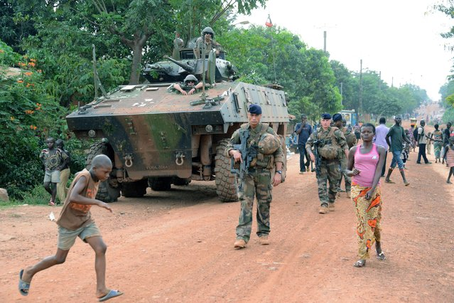 "French soldiers patrol a street in Bangui, part of ""Operation Sangaris"", on May 2, 2015. Faced with mounting pressure to shed light on accusations that French soldiers sexually abused children in the Central African Republic, the United Nations said May 1, 2015 suggestions of a cover-up were ""offensive"". (Photo by Pacome Pabandji/AFP Photo)"