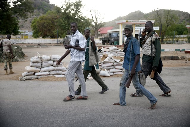 Local vigilantes walk while holding guns at a military checkpoint in the town of Gombi after the Nigerian military recaptures the surrounding towns from Boko Haram, Adamawa state May 10, 2015. (Photo by Akintunde Akinleye/Reuters)