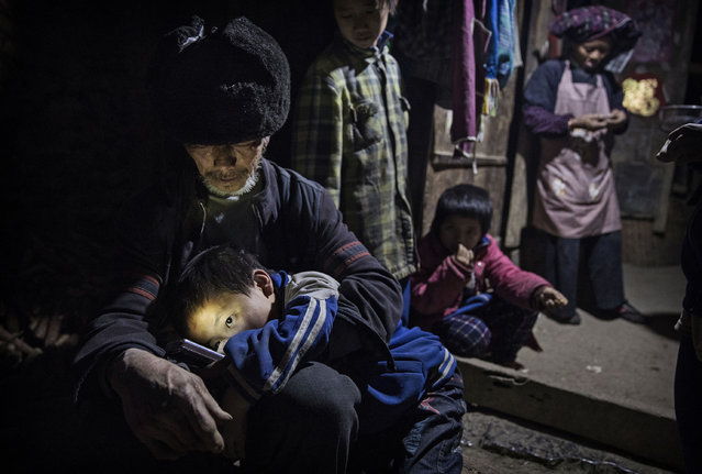"""Grandfather Luo Yingtao, 64, holds his grandson """"left behind"""" child Luo Lie, 5, in his lap as they sit at the family house on December 15, 2016 in Anshun, China. (Photo by Kevin Frayer/Getty Images)"""