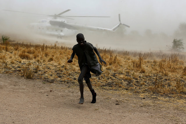 A boy moves away as a United Nations World Food Programme (WFP) helicopter lands in Rubkuai village, Unity State, northern South Sudan, February 18, 2017. (Photo by Siegfried Modola/Reuters)