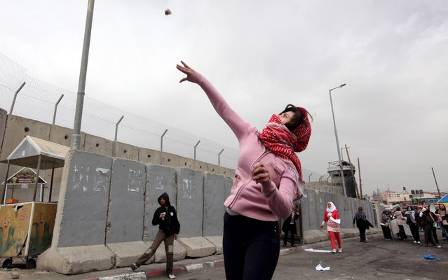 A Palestinian woman throws a stone towards Israeli troops at Qalandia checkpoint between Jerusalem and the West Bank city of Ramallah, Saturday, March 8, 2014. Palestinian women marked International Women's Day by marching to the checkpoint where clashes broke out with Israeli troops. (Photo by Majdi Mohammed/AP Photo)