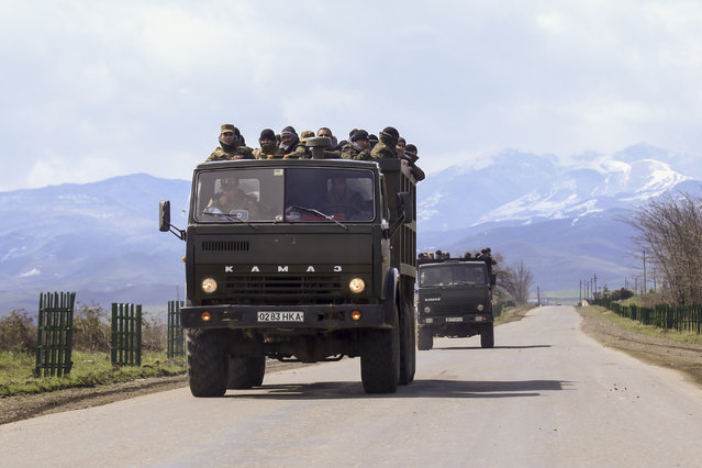 Ethnic Armenian fighters stand in backs of Kamaz military trucks on their way to a frontline at Martakert province in the separatist region of Nagorno-Karabakh, Azerbaijan, Monday, April 4, 2016. Fighting raged Monday around Nagorno-Karabakh, with Azerbaijan saying it lost three of its troops in the separatist region while inflicting heavy casualties on Armenian forces and the Armenian president warning that the hostilities could slide into a full-scale war. (Photo by Hrayr Badalyan/PAN Photo via AP Photo)