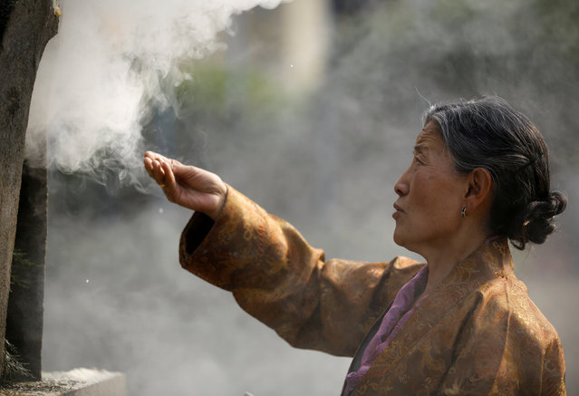 """A woman offers incense during a function organised to mark """"Losar"""", or the Tibetan New Year, in Kathmandu, Nepal March 1, 2017. (Photo by Navesh Chitrakar/Reuters)"""