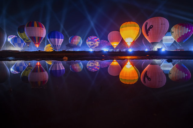 "This image released on Friday, February 8, 2019 shows a scene during the 2019 AlUla Balloon Festival part of Winter at Tantora in Al-Ula, Saudi Arabia. Sixty hot air balloons took to the sky in the region's first Hot Air Balloon Festival offering rides to festival goers and locals alike. Each night the balloons light up the night skies with a daily ""glow show"". (Photo by Hussain Daghiri/Winter At Tantora via AP Images)"