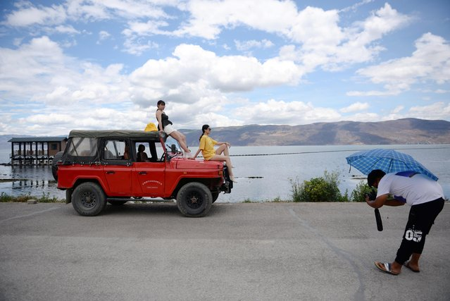 Women sit atop a vehicle as they pose for photos during a photoshoot session near Erhai Lake in Dali Bai Autonomous Prefecture, Yunnan province, China on June 15, 2019. (Photo by Tingshu Wang/Reuters)