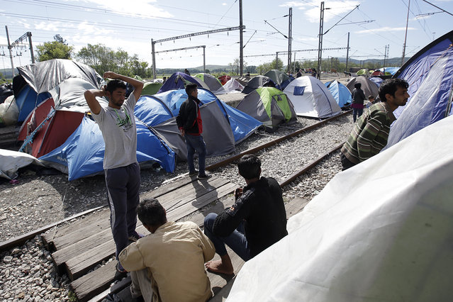 Migrants and refugees gather near their tents set on the tracks of a railway station turned into a makeshift camp at the northern Greek border point of Idomeni, Greece, Monday, April 25, 2016. Many thousands of migrants remain at the Greek border with Macedonia, hoping that the border crossing will reopen, allowing them to move north into central Europe. (Photo by Gregorio Borgia/AP Photo)