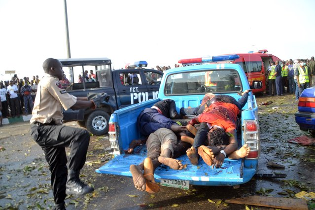 A man puts dead bodies, victims of an attack, in a car to be taken to the morgue in Abuja on April 14, 2014. Twin blasts at a bus station packed with morning commuters on the outskirts of Nigeria's capital killed dozens of people on April 14, in what appeared to be the latest attack by Boko Haram Islamists. (Photo by AFP Photo/STR)