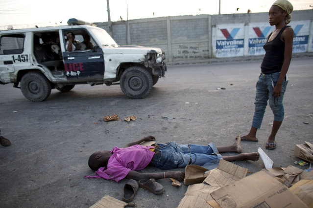 Police who were passing by stop briefly to get information about a body lying amidst trash on the street, in central Port-au-Prince, Haiti, Sunday, June 28, 2015. Neighborhood residents said the young man had been intoxicated and collapsed nearby. With no one able to identify him, residents carried his body to a trash pile along the main road. (Photo by Rebecca Blackwell/AP Photo)