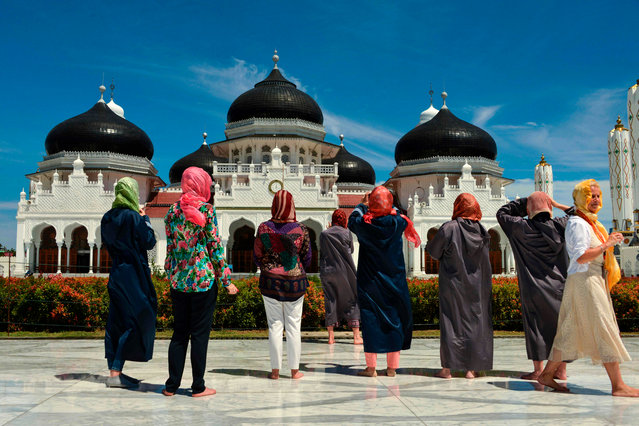 Foreign visitors wear the hijab during a visit to Baiturrahman grand mosque in Banda Aceh on August 6, 2019. (Photo by Chaideer Mahyuddin/AFP Photo)
