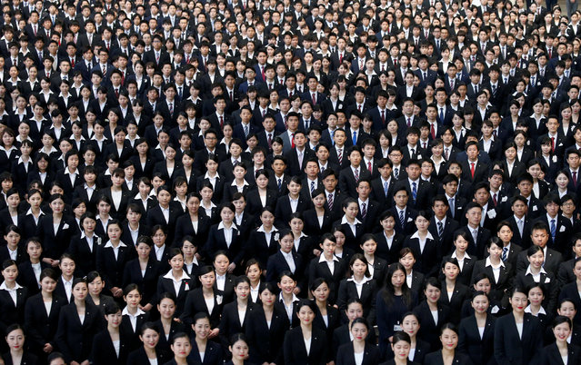 Newly-hired employees of Japan Airlines (JAL) group pose for photos during an initiation ceremony at a hangar of Haneda airport in Tokyo, Japan, April 3, 2017. (Photo by Toru Hanai/Reuters)