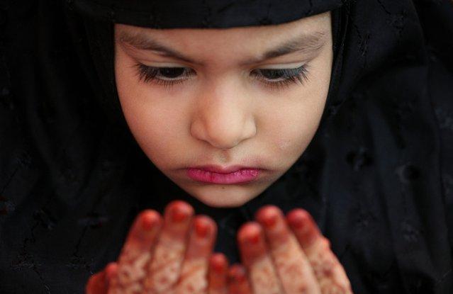 A Muslim girl offers an Eid al-Adha prayer at a mosque in Chennai, August 12, 2019. (Photo by P. Ravikumar/Reuters)