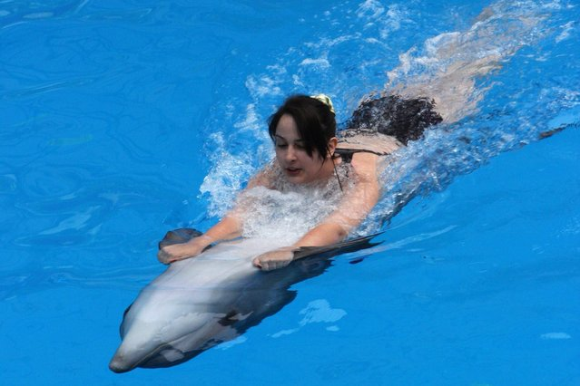 A trained dolphin interacts with a girl during a dolphin therapy session in a dolphinarium in the Crimean resort town of Alushta, on April 24, 2014. (Photo by Yuriy Lashov/AFP Photo)