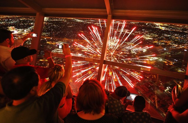 Spectators watch Fourth of July fireworks from the Stratosphere hotel and casino, Saturday, July 4, 2015, in Las Vegas. (Photo by John Locher/AP Photo)