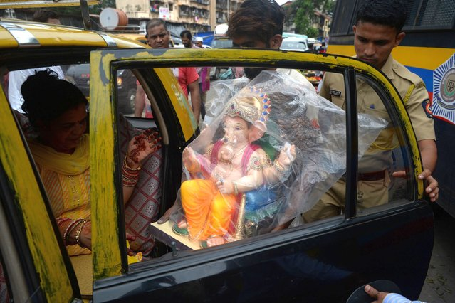 Devotees transport an idol of the elephant-headed Hindu deity Ganesha for Ganesh Chaturthi in Mumbai on September 2, 2019. The Ganesh Chaturthi festival, a popular 11-day religious festival which is annually celebrated across India, runs this year from September 2 to 12, and culminates with the immersion of idols of Ganesh in the Arabian Sea and local water bodies. (Photo by Punit Paranjpe/AFP Photo)