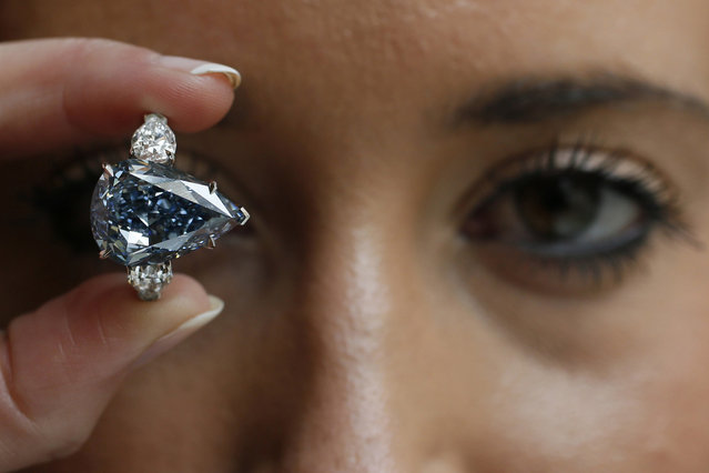 "An employee poses with ""The Blue"" diamond at Christie's auction house in London April 29, 2014. Christie's London is displaying the largest flawless fancy vivid blue diamond ever to appear at auction. The diamond is pegged at $21 million to $25 million and is the highlight of an upcoming Magnificent Jewels sale in Geneva. (Photo by Stefan Wermuth/Reuters)"