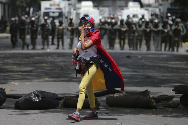 A demonstrator walks along a barricade set up during opposition protesters in Caracas, Venezuela, Wednesday, April 19, 2017. (Photo by Fernando Llano/AP Photo)