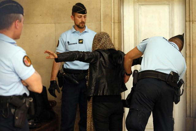 "French gendarmes searches a woman as she arrives to attend the ruling in the case of 14 members of a banned Islamic group tried on charges of ""criminal conspiracy related to a terrorist enterprise"" at the Paris court house, France, July 10, 2015. (Photo by Charles Platiau/Reuters)"