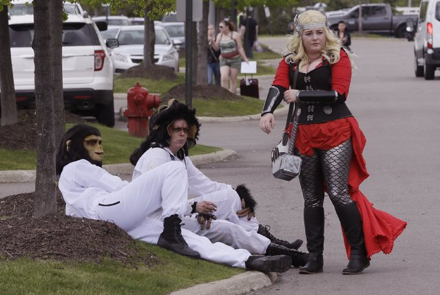 From left, Sean Baumgartner as Cornelius and Rhonda Payne as Caesar from Planet of the Apes, and Katey Griffin as Thor, take a break outside the Motor City Comic Con, Friday, May 13, 2016 in Novi, Mich. (Photo by Carlos Osorio/AP Photo)