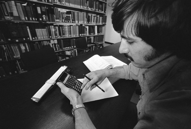 Steven F. Manzi of Cranston, R.T., a graduate student at the Massachusetts Institute of Technology, uses a calculator in his studies as an engineer at MIT in Cambridge, Massachusetts, February 10, 1976. The old slide rule formerly used in his work is at lower left of the photo. (Photo by AP Photo)