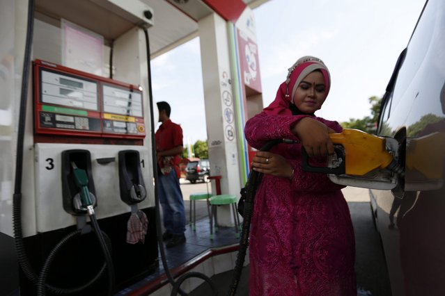 "A fuel-station woman employee with an Indonesian traditional dress known as ""kebaya"", fills petrol into a vehicle during the Kartini Day celebrations in Banda Aceh, Indonesia, 21 April 2016. Kartini was a prominent Javanese woman regarded as an Indonesian national heroine and a pioneer in the area of education for girls as well as for promoting women's rights. Kartini Day is celebrated yearly on Kartini's birthday, 21 April. (Photo by Hotli Simanjuntak/EPA)"