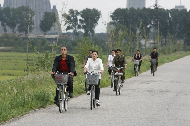 North Koreans ride their bicycles outside Pyongyang August 27, 2007. (Photo by Reinhard Krause/Reuters)