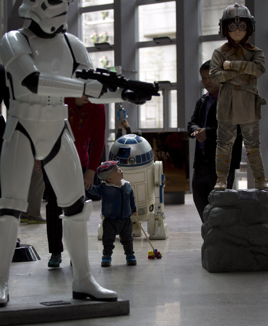A child walks near the life-size characters figures of the Star Wars movies on display at a shopping mall in Beijing, China Sunday, May 11, 2014. (Photo by Andy Wong/AP Photo)