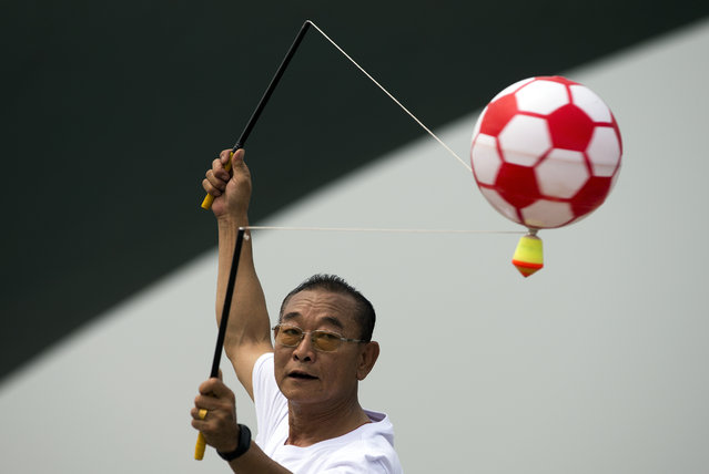 In this Sunday, June 28, 2015 photo, a man spins a top mount with an inflatable ball during a public sport campaign to promote exercise at Garden Expo Park in Beijing. (Photo by Andy Wong/AP Photo)