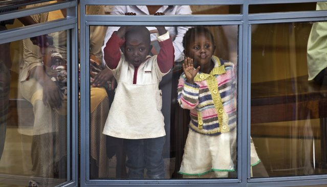 Two Kenyan children look out from an upper level in the reopened Westgate Shopping Mall, nearly two years after a terrorist attack there left at least 67 people dead, in the capital Nairobi, Kenya Saturday, July 18, 2015. Hundreds of shoppers thronged through the reopened mall Saturday, following two years of repairs after security forces battled four gunmen from Somalia's al-Qaida-linked al-Shabab militant group there in September 2013. (Photo by Ben Curtis/AP Photo)