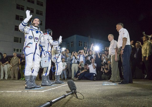 The International Space Station (ISS) crew members (L to R) Kjell Lindgren of the U.S., Oleg Kononenko of Russia and Kimiya Yui of Japan wave after donning space suits at the Baikonur cosmodrome, Kazakhstan, July 23, 2015. (Photo by Shamil Zhumatov/Reuters)