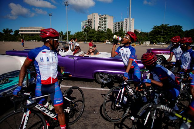 Members of the Haiti national cycling team take a break from a training session in front of a vintage car with tourists in Havana, Cuba, November 1, 2019. Cycling is not an easy sport to practice in Haiti, a country wracked by poverty, natural catastrophes and political instability. But change is afoot after a competition in Havana, where Haiti's national team put in their best performance ever at the Caribbean Road Cycling Championship, thanks to a new program created by the Union Cycliste Internationale (UCI) that fosters the sport in small, developing nations. (Photo by Alexandre Meneghini/Reuters)