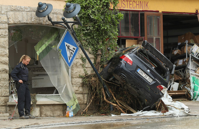 A policewoman stands near a car smashed against a building in the village center following a ferocious flash flood the night before on May 30, 2016 in Braunsbach, Germany. The flood tore through Braunsbach, crushing cars, ripping corners of houses and flooding homes during a storm that hit southwestern Germany. Miraculously no one in Braunsbach was killed, though three people died as a result of the storm in other parts of the country. (Photo by Sean Gallup/Getty Images)