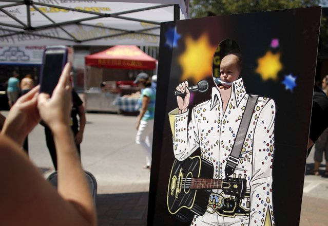 Eleven week-old baby girl Alyssa Malfatti of Orangeville, Ontario is held by her father for a portrait in an Elvis cutout during the four-day Collingwood Elvis Festival in Collingwood, Ontario July 26, 2015. (Photo by Chris Helgren/Reuters)