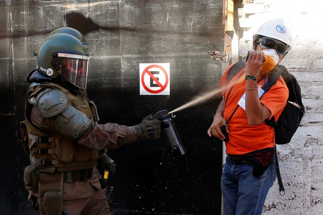 A member of the security forces uses pepper spray towards a human rights' observer during a protest against Chile's government in Valparaiso, Chile November 26, 2019. (Photo by Rodrigo Garrido/Reuters)