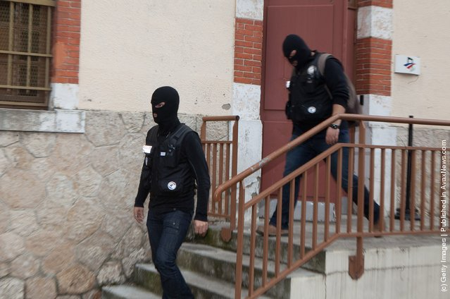 Masked officers stand by as police continue to surround a property during an operation to arrest 24-year-old Mohammed Merah, the man suspected of killing seven victims including three children in separate gun attacks
