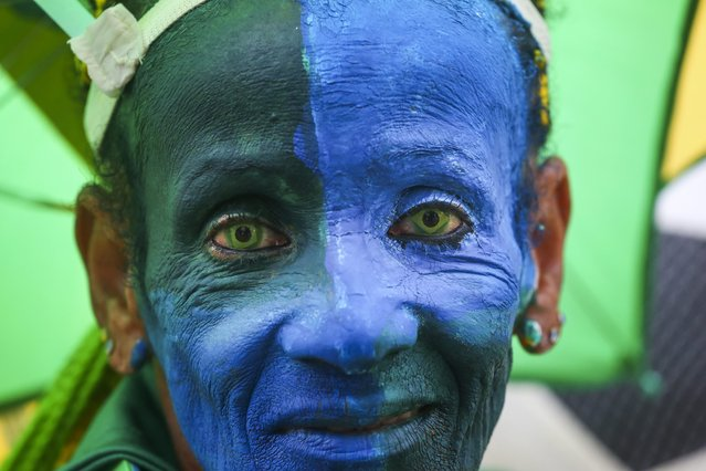 Brazilian fan Ana Luiza dos Anjos wearing contact lenses with the Brazilian national flag and her face painted blue before the FIFA World Cup 2014 group A preliminary round match between Brazil and Mexico at the FIFA Fan Fest in Sao Paulo, Brazil, 17 June 2014. The match at the Estadio Castelao in Fortaleza ended 0-0. (Photo by Diego Azubel/EPA)
