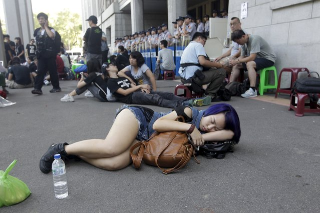 "A student (front) sleeps on the ground during a protest at the entrance to the Ministry of Education in Taipei, Taiwan, July 31, 2015. Hundreds of Taiwan students stormed the ministry of education compound early on Friday, after one committed suicide earlier in the week, intensifying anti-China protests over textbooks they say are aimed at promoting Beijing's ""one China"" policy. (Photo by Pichi Chuang/Reuters)"